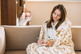Young woman with notepad and pen on sofa