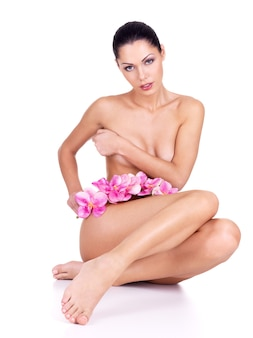Young woman with nude body sits on the white with flowers