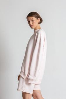 ヌードメイクの若い女性は、白い背景の上のピンクの特大のパーカーとショートパンツでポーズをとる