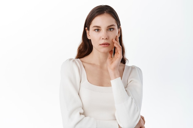 Young woman with nude natural make up, touching hydrated clean facial skin, holding hand on cheek, gazing at front thoughtful, white wall