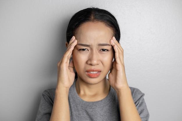 灰色のストレスと頭痛の若い女性。