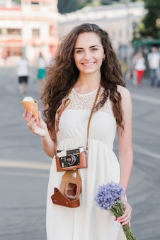 Young woman with old camera ice cream and flowers