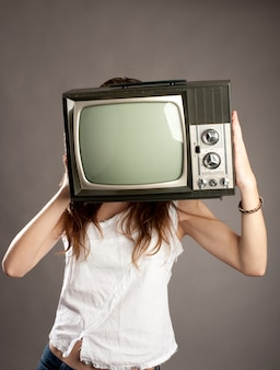 Young woman with old retro tv