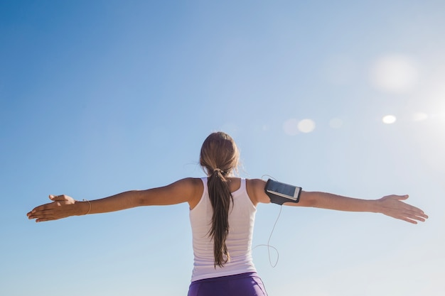 Young woman with open arms after training