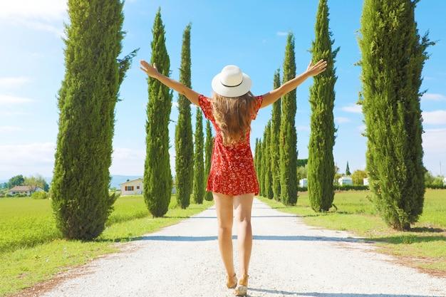 トスカーナのイタリアの田舎の糸杉の車線で両手を広げて若い女性
