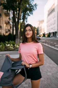 通りでオープンバックパックを持つ若い女性。若い女性の肖像画