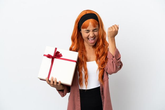 Молодая женщина с оранжевыми волосами, держащая подарок на белом фоне, празднует победу