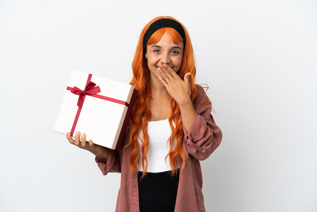 白い背景で隔離の贈り物を保持しているオレンジ色の髪の若い女性幸せと笑顔の手で口を覆う
