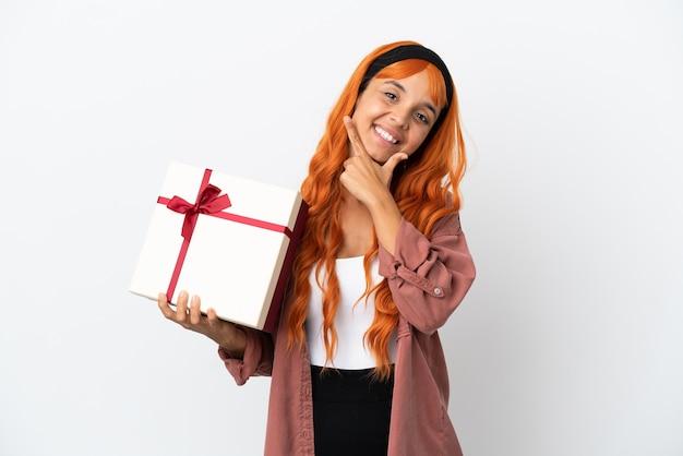 Молодая женщина с оранжевыми волосами, держащая подарок на белом фоне, счастлива и улыбается