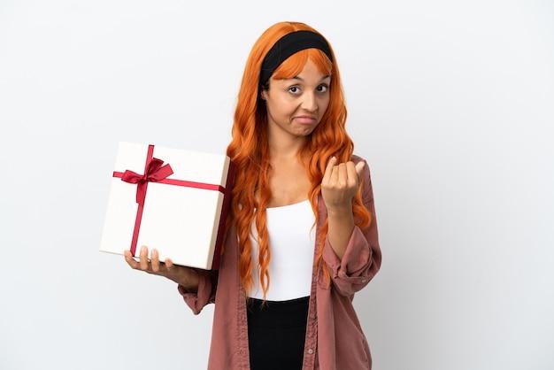 手で来るように誘う白い背景で隔離の贈り物を保持しているオレンジ色の髪の若い女性。あなたが来て幸せ