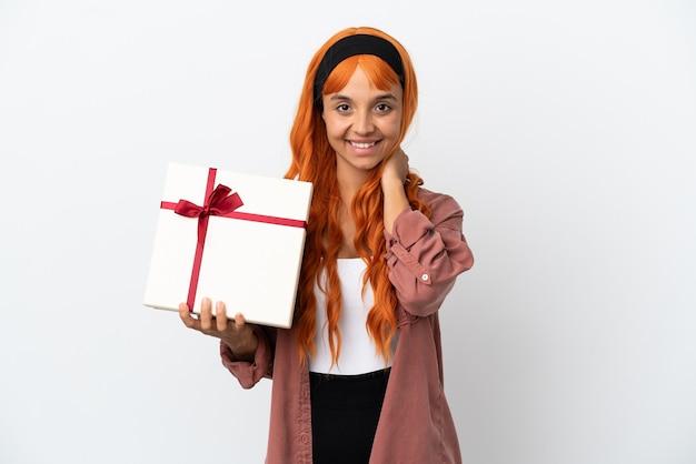 Молодая женщина с оранжевыми волосами держит подарок на белом фоне смеется