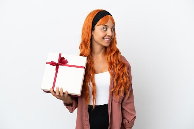 Молодая женщина с оранжевыми волосами держит подарок на белом фоне, глядя в сторону и улыбается