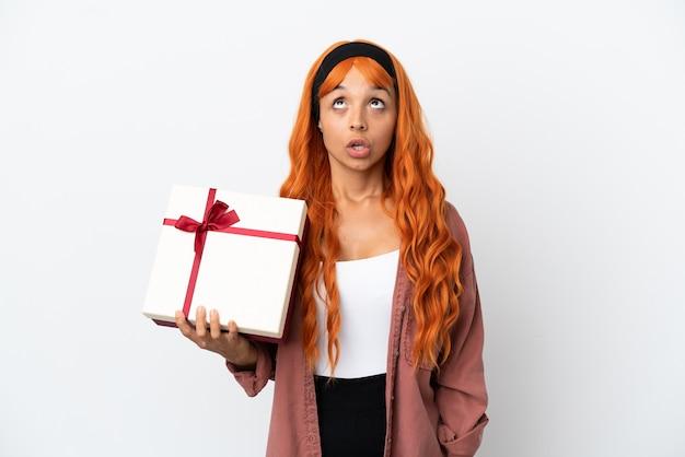 Молодая женщина с оранжевыми волосами держит подарок на белом фоне, глядя вверх и с удивленным выражением лица
