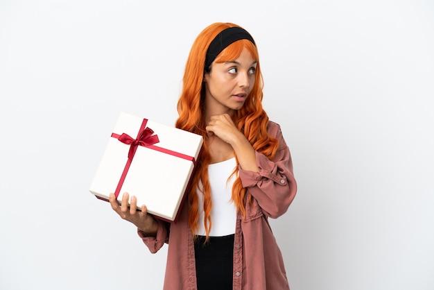Молодая женщина с оранжевыми волосами держит подарок на белом фоне, глядя вверх, улыбаясь