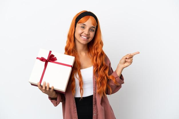 Молодая женщина с оранжевыми волосами держит подарок на белом фоне, указывая пальцем в сторону