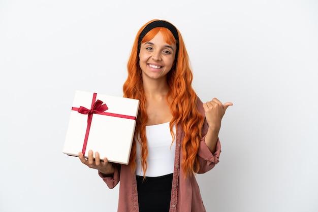 Молодая женщина с оранжевыми волосами держит подарок на белом фоне, указывая в сторону, чтобы представить продукт