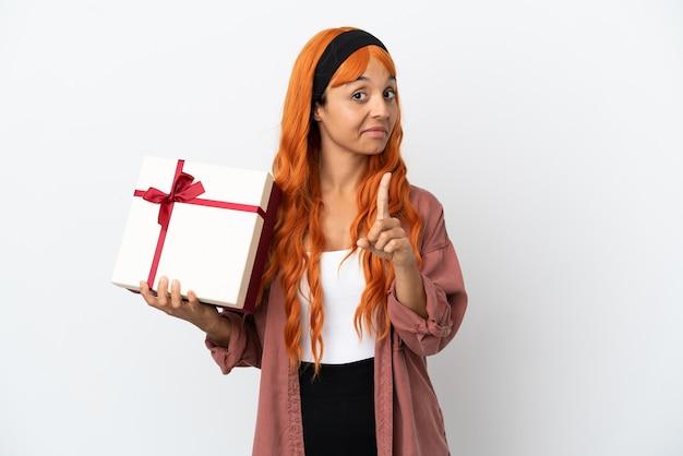 Молодая женщина с оранжевыми волосами держит подарок на белом фоне, показывая и поднимая палец