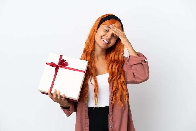 Молодая женщина с оранжевыми волосами держит подарок на белом фоне, много улыбаясь