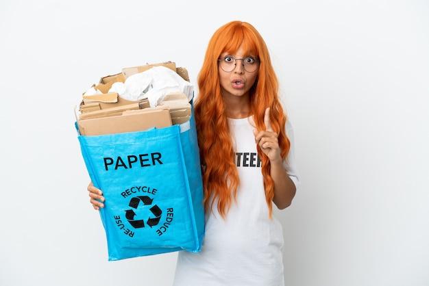 Молодая женщина с оранжевыми волосами держит мешок для переработки, полный бумаги для переработки, изолированную на белом фоне, намереваясь реализовать решение, подняв палец вверх