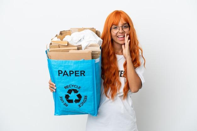 Молодая женщина с оранжевыми волосами, держащая мешок для переработки, полный бумаги для переработки, изолирована на белом фоне, кричит с широко открытым ртом