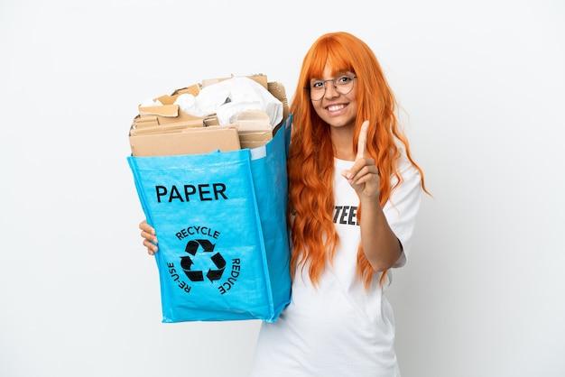 Молодая женщина с оранжевыми волосами держит мешок для рециркуляции, полный бумаги для переработки, изолированную на белом фоне, показывая и поднимая палец