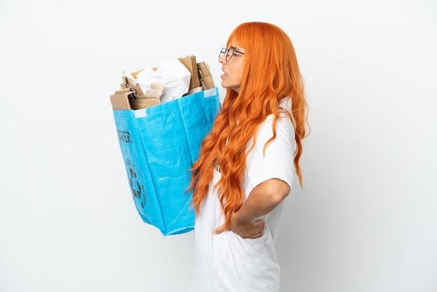 흰색 배경에 격리된 재활용 종이로 가득 찬 재활용 가방을 들고 주황색 머리를 한 젊은 여성은 노력을 해서 요통으로 고통받고 있다