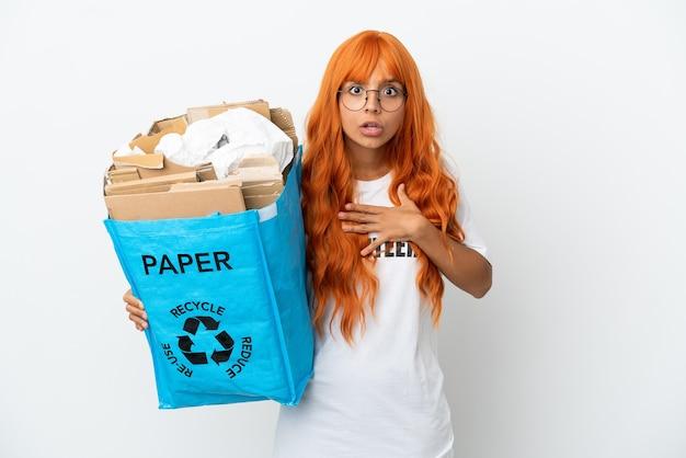 白い背景で隔離のリサイクルする紙でいっぱいのリサイクルバッグを保持しているオレンジ色の髪の若い女性は、右を見ながら驚いてショックを受けました