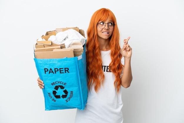 Молодая женщина с оранжевыми волосами держит мешок для переработки, полный бумаги для переработки, изолированную на белом фоне, скрестив пальцы и желая всего наилучшего
