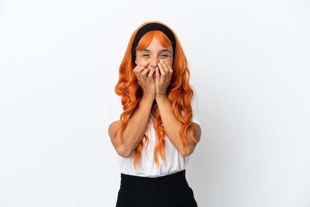 オレンジ色の髪の若い女性が白い背景で隔離の幸せと笑顔で口を手で覆う