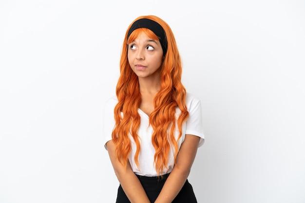側面を見ながら疑問を持っている白い背景で隔離オレンジ色の髪の若い女性