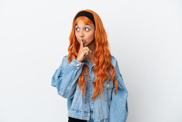 Молодая женщина с оранжевыми волосами, изолированными на белом фоне, показывает знак жеста молчания, кладя палец в рот