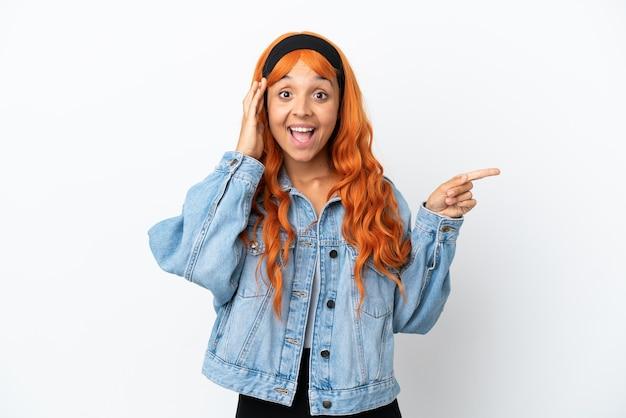 Молодая женщина с оранжевыми волосами на белом фоне удивлена и показывает пальцем в сторону