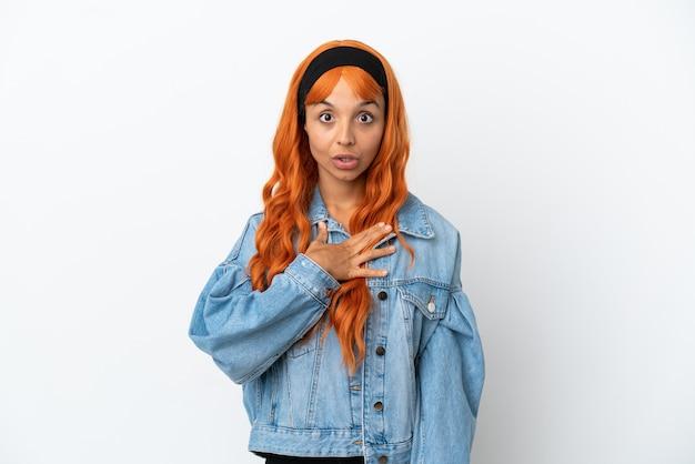 白い背景に分離されたオレンジ色の髪の若い女性は、右を見ながら驚いてショックを受けました