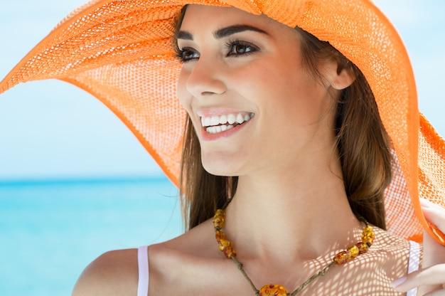 海でオレンジ色の帽子を持つ若い女性