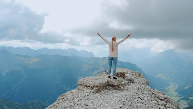 Молодая женщина с протянутыми руками, наслаждаясь красотой природы на горной скале. фантастический пейзажный вид.