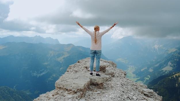 Молодая женщина с протянутыми руками, наслаждаясь красотой природы на горной скале