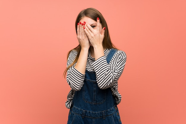 Young woman with overalls over pink wall covering eyes by hands and looking through the fingers