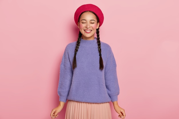 Young woman with overjoyed expression, keeps eyes shut, wears red beret, warm purple sweater and plaited skirt, gets pleasure from receiving compliment, poses over pink wall