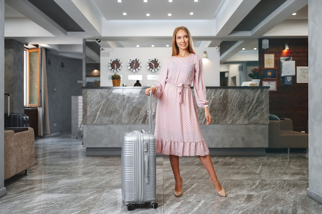 Young woman with packed suitcase standing in hotel lobby close up