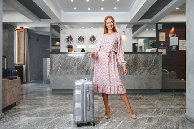 Молодая женщина с упакованным чемоданом стоя в холле отеля крупным планом