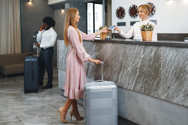 ホテルのロビーに立っているパックされたスーツケースを持つ若い女性