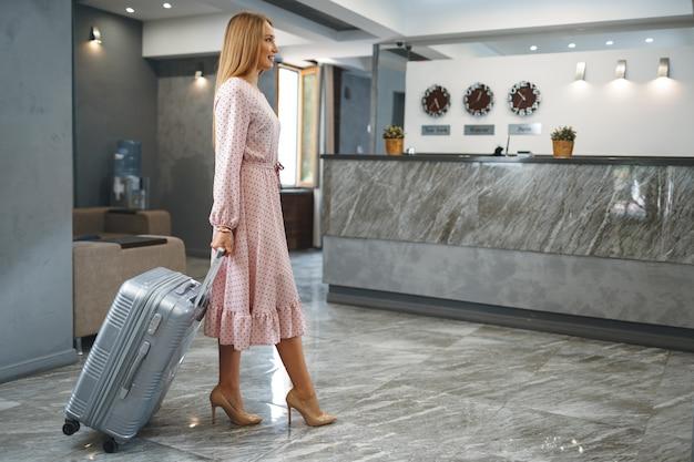 Молодая женщина с упакованным чемоданом, стоя в холле отеля