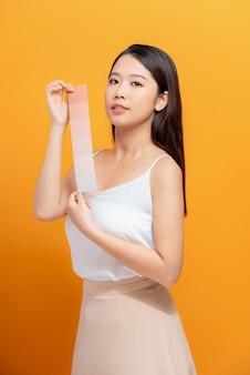 色の背景にペイントパレットを持つ若い女性