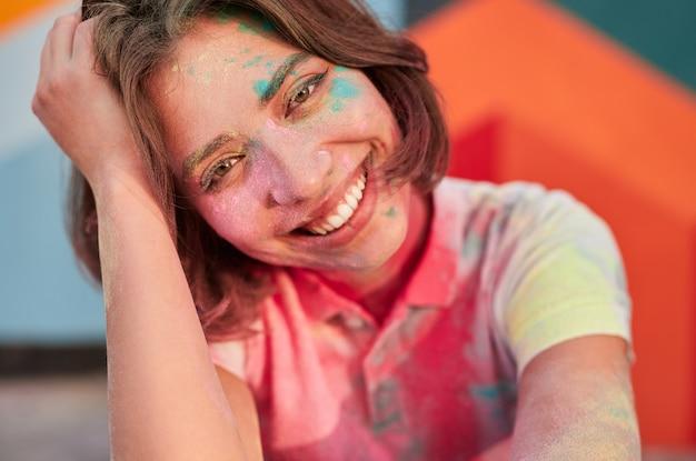笑顔の顔にペンキの粉を持つ若い女性
