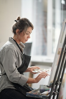 Молодая женщина с кистью и цветовой палитрой работает над новой картиной на уроке в школе или студии искусств