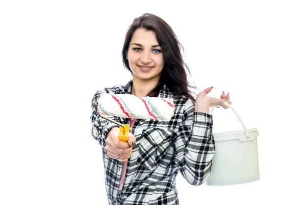 白で隔離の絵画ツールを持つ若い女性