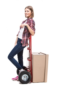 Young woman with paper box and a hand truck.