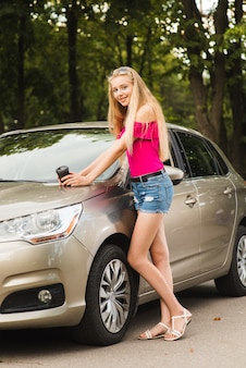 Young woman with paper cup near car