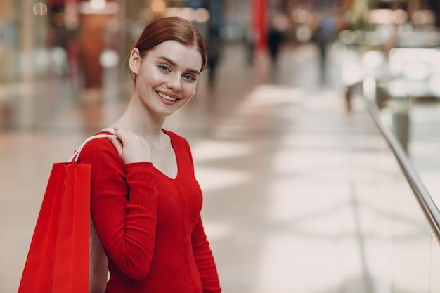 쇼핑몰에서 종이 빨간 가방 젊은 여자. 검은 금요일과 발렌타인 데이 개념.