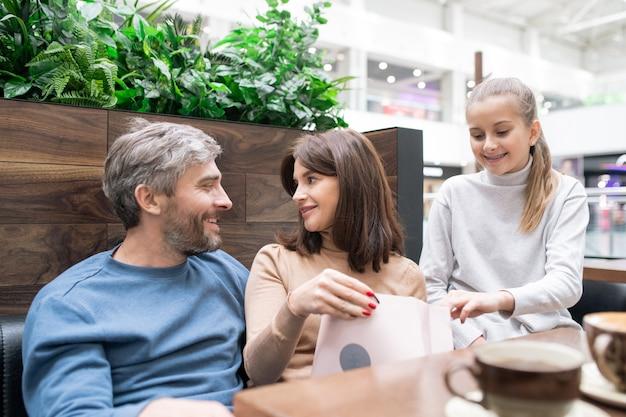 Paperbagを持つ若い女性と彼女の夫が近くに座って、バッグの中身を見て娘と購入について話し合う